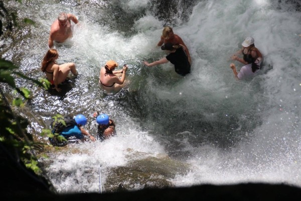 Group playing in the waterfall